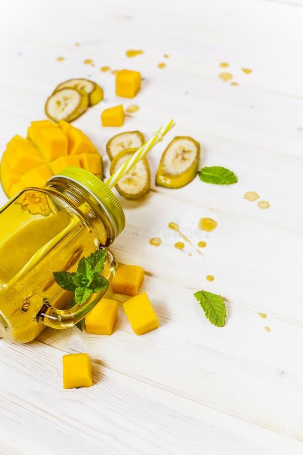 Mango en banaan smoothie in metselaarkruik met stro royalty-vrije stock afbeelding