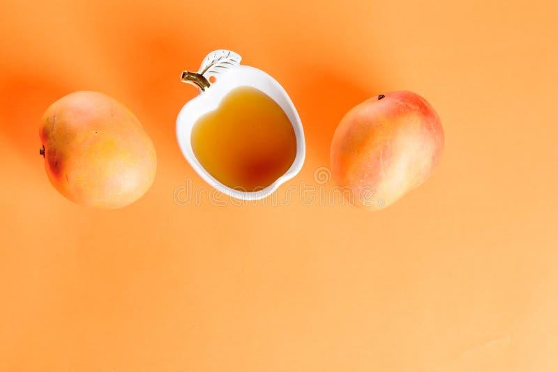 Mango en honing op oranje achtergrond royalty-vrije stock foto's
