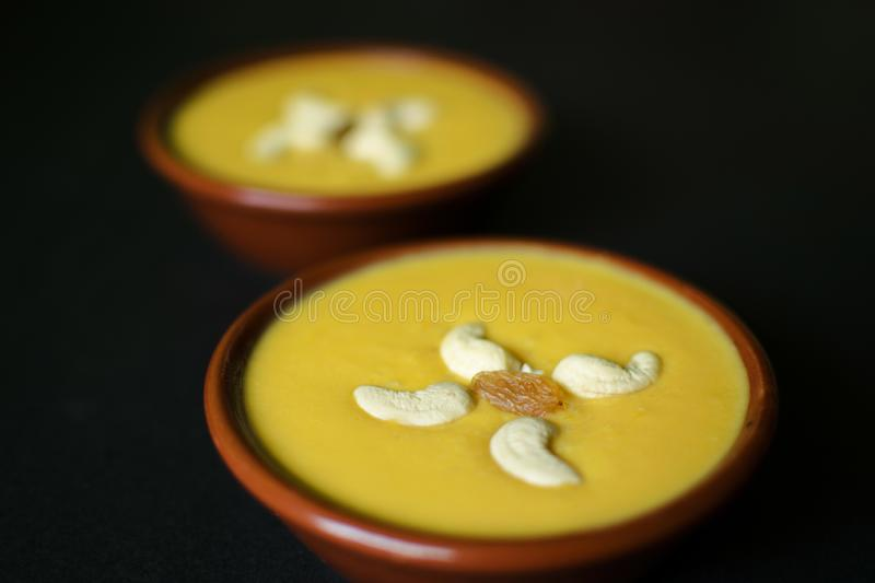 Mango firni a traditional dessert from India garnished with cashew nuts on black surface royalty free stock photography