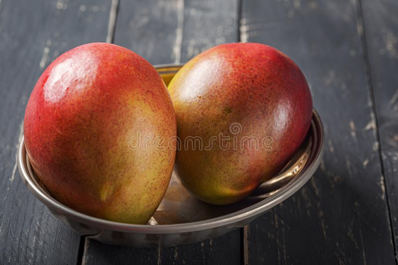 Mango fresh fruit on black wooden table. Two whole mango fruits on wood dark background. Clean eating ingredients and healthy food concept. minimal, selective stock photo