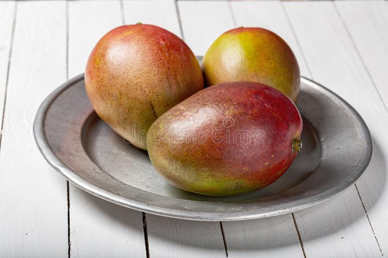 Mango fresh fruit on white wooden table. Whole mango fruit in a plate on wood white background. Clean eating ingredients and healphy food cincept. minimal stock photo