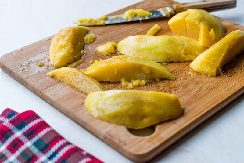 Mango-Frucht-Scheiben schnitten mit Messer auf Holzoberfläche-Brett lizenzfreies stockfoto