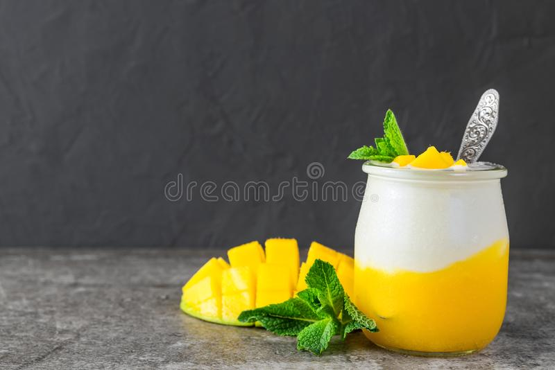 Mango fruit yogurt with fresh mint in a glass with a spoon over black concrete background. healthy breakfast. Close up stock photos