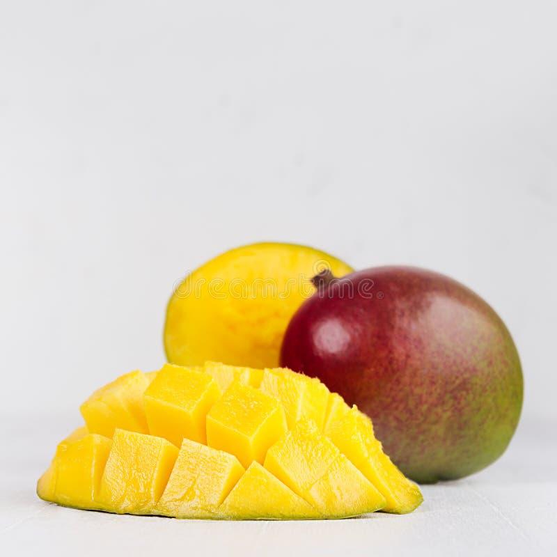 Mango giallo maturo intero con il lato rosso e verde ed il mezzo primo piano affettato polposo sul bordo di legno bianco molle, q fotografie stock