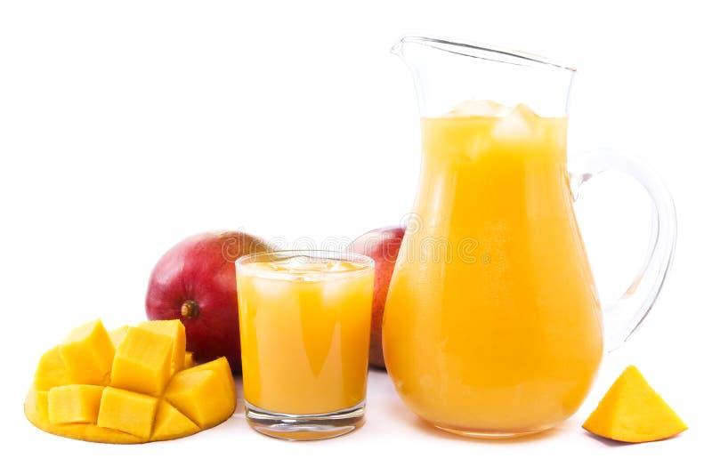 Mango juice. Glass and jug full of fresh cold mango juice and ice cubes decorated with mangos stock photos