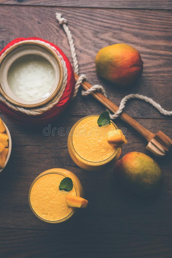 Mango Lassi of smoothie in groot glas of kleine flessen met gestremde melk, de stukken van het besnoeiingsfruit en mixer stock foto's