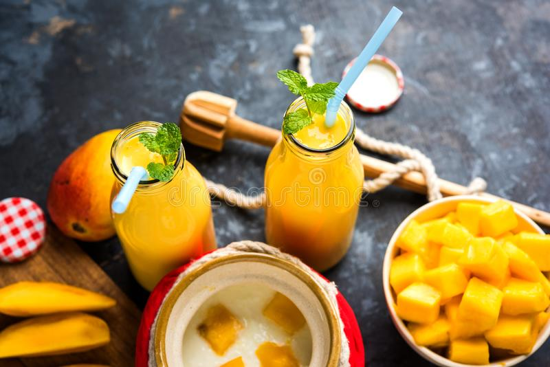 Mango Lassi of smoothie in groot glas of kleine flessen met gestremde melk, de stukken van het besnoeiingsfruit en mixer stock afbeelding
