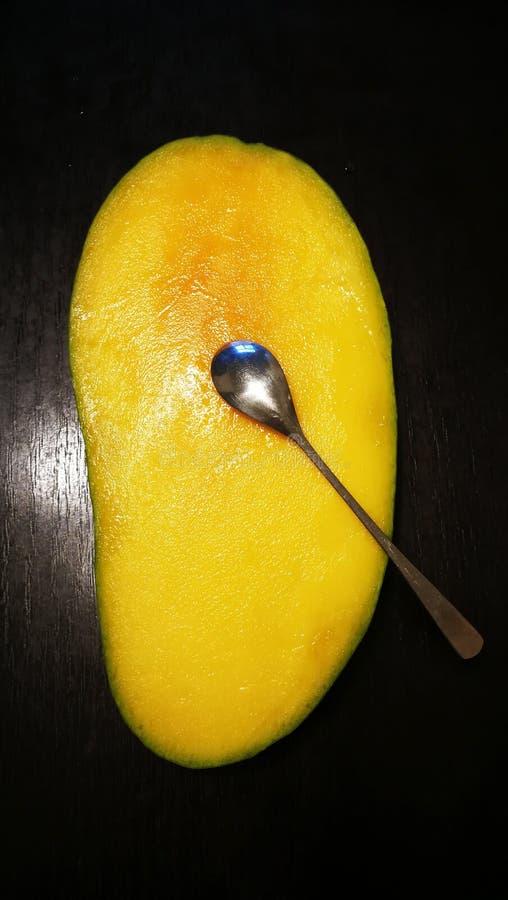 Mango met een lepel stock afbeeldingen