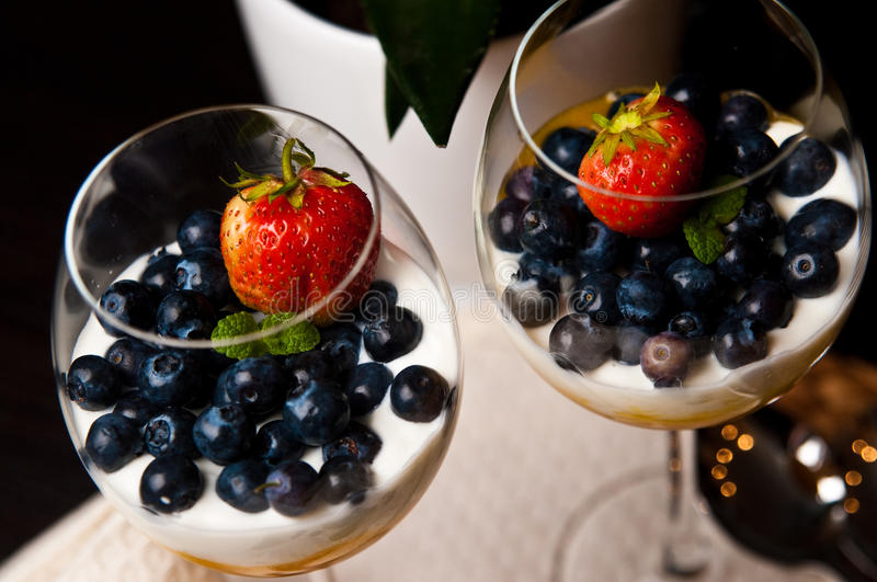 Mango mousse with blueberries in wine glasses. Tasty dessert of mango mousse with natural youghurt, blueberries and strawberry. Whole series with sebczseries953 stock photos