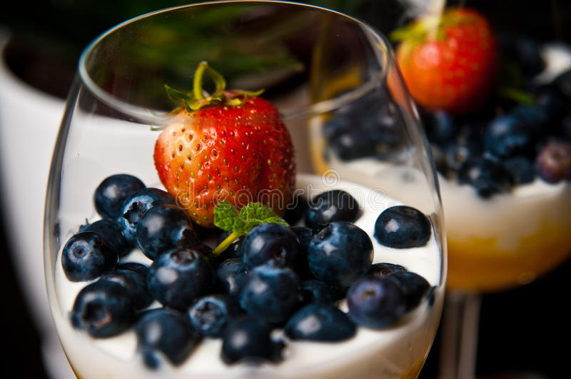 Mango mousse with blueberries in wine glasses. Tasty dessert of mango mousse with natural youghurt, blueberries and strawberry. Whole series with sebczseries953 royalty free stock images