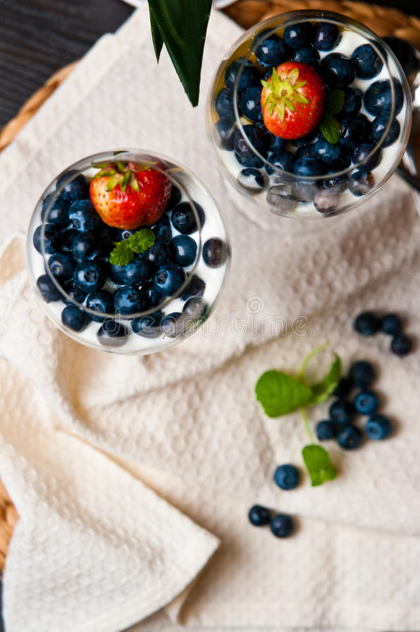Mango mousse with blueberries in wine glasses. Tasty dessert of mango mousse with natural youghurt, blueberries and strawberry. Whole series with sebczseries953 stock photo
