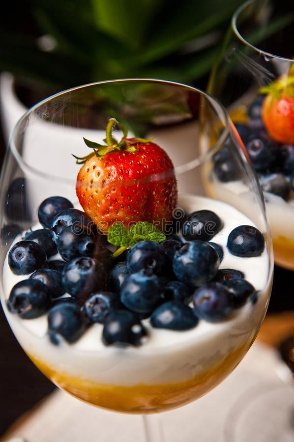 Mango mousse with blueberries in wine glasses. Tasty dessert of mango mousse with natural youghurt, blueberries and strawberry. Whole series with sebczseries953 royalty free stock image