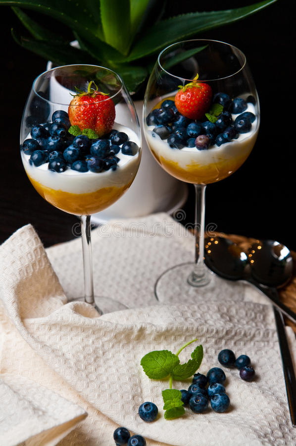 Mango mousse with blueberries in wine glasses. Tasty dessert of mango mousse with natural youghurt, blueberries and strawberry. Whole series with sebczseries953 stock images