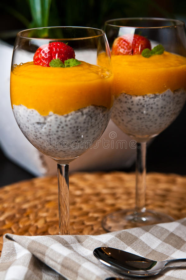 Mango mousse with chia seeds and coconut milk. An elegant table setting with homemade mango mousse with chia seeds, coconut milk, natural yoghurt, maple syrup stock image