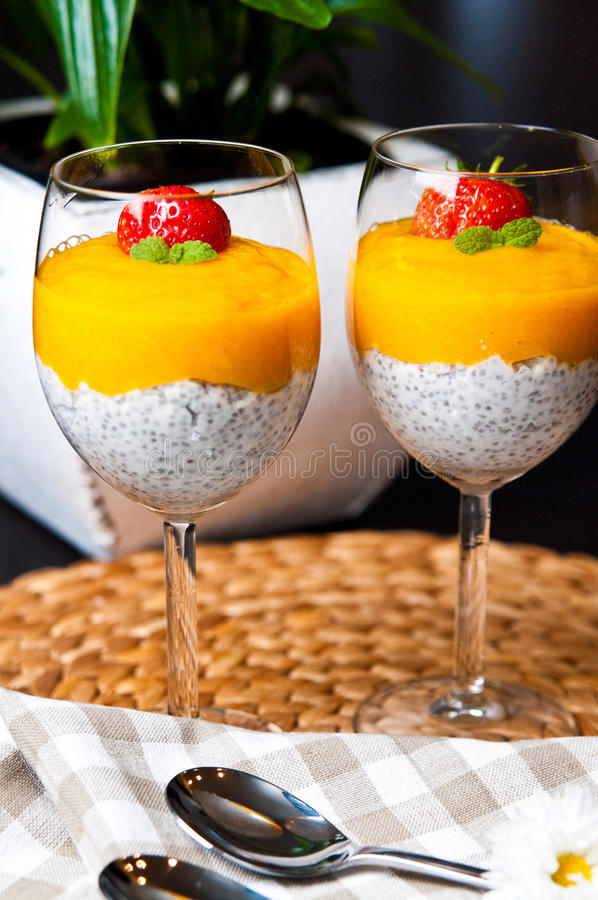 Mango mousse with chia seeds and coconut milk. An elegant table setting with homemade mango mousse with chia seeds, coconut milk, natural yoghurt, maple syrup stock photo