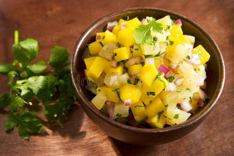 Mango pineapple salsa. In a wooden bowl royalty free stock photo