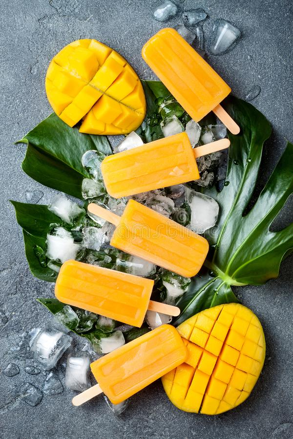 Mango popsicles over green tropical palm leaf on grey stone background. royalty free stock photo