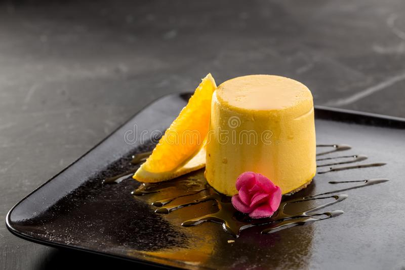 Mango pudding jelly dessert on black plate on black background royalty free stock photo