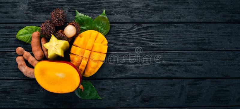 Mango, rambutan och tamarindfrukt tropiska nya frukter P? en tr?bakgrund arkivfoton