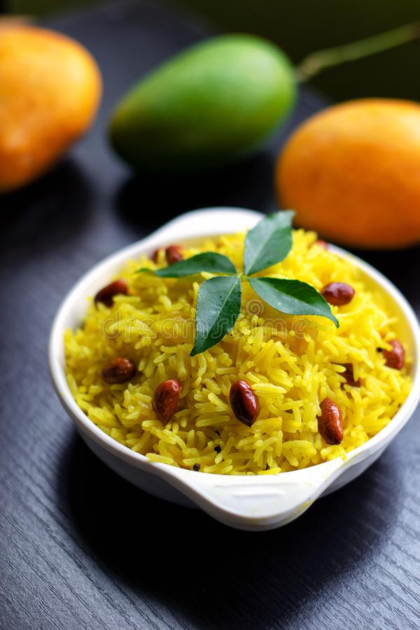 Mango rice in bowl , an Indian dish garnished with curry leaves & roasted peanut with raw ripe mangoes in the background on black stock images