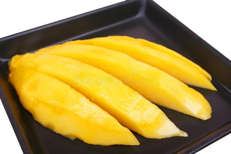 Mango's op zwarte die plaat op witte achtergrond wordt geïsoleerd stock afbeeldingen