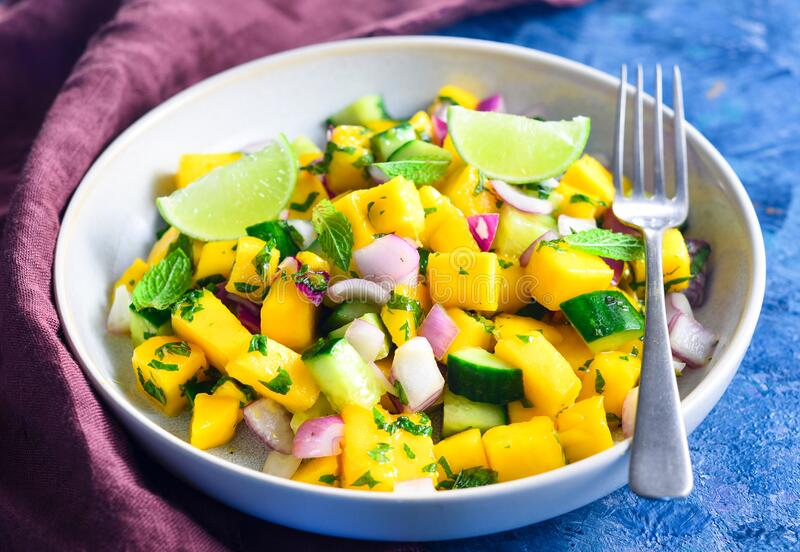 Mango salsa salad bowl with fork stock photos