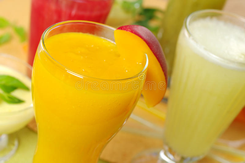 Mango Smoothie. Fresh mango smoothie surrounded by watermelon, kiwi and pineapple smoothies and a cream cheese dessert on the left (Selective Focus, Focus on the royalty free stock photography