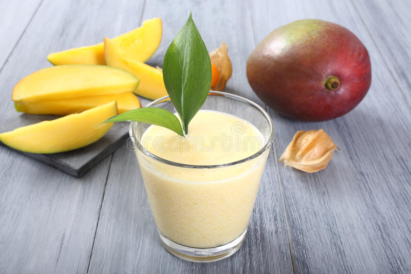 Mango smoothie. Closeup glass with mango smoothie on gray background royalty free stock images