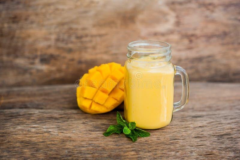 Mango smoothie in een kruik van de glasmetselaar en mango op de oude houten achtergrond Mangoschok stock fotografie