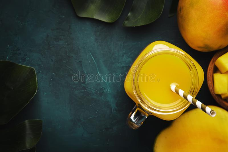 Mango smoothie in glass jar with fresh fruit on blue background, copy space, top view stock images