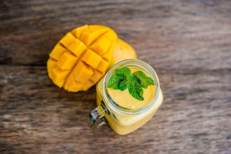 Mango smoothie in a glass Mason jar and mango on the old wooden background. Mango shake. stock image