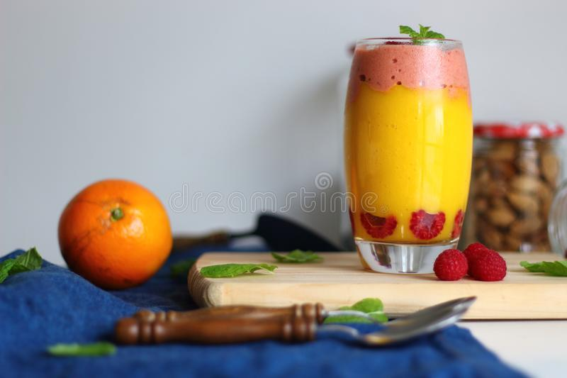 Mango smoothie in glass with raspberry ice cream and mint. stock images