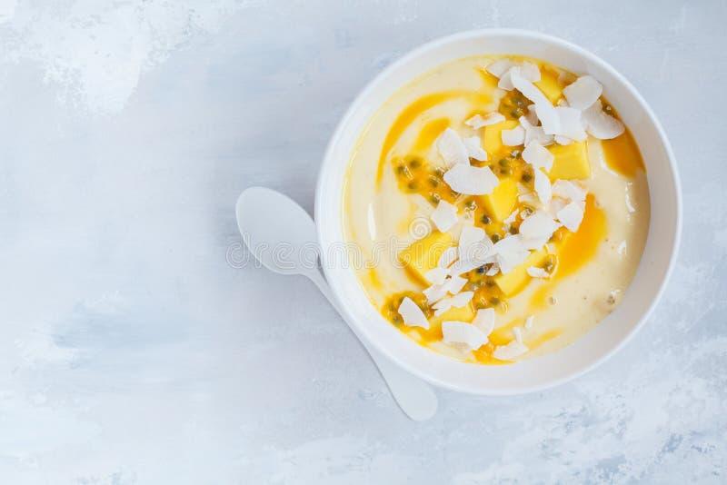 Mango smoothie kom met kokosnoot en passievrucht stock afbeeldingen
