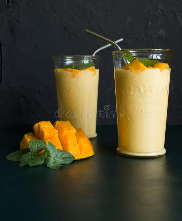 Mango smoothie / mango lassi in vintage glass cups on a dark surface with metal straws. with mint leaves and a slice of ripe and j. Uicy mango royalty free stock photo