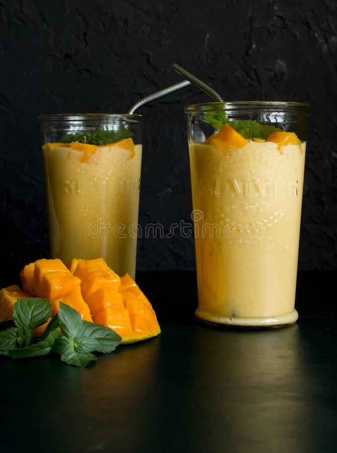 Mango smoothie / mango lassi in vintage glass cups on a dark surface with metal straws. with mint leaves and a slice of ripe and j. Juicy mango smoothie / mango royalty free stock photo