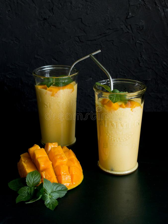Mango smoothie / mango lassi in vintage glass cups on a dark surface with metal straws. with mint leaves and a slice of ripe and j. Juicy mango smoothie / mango stock photo