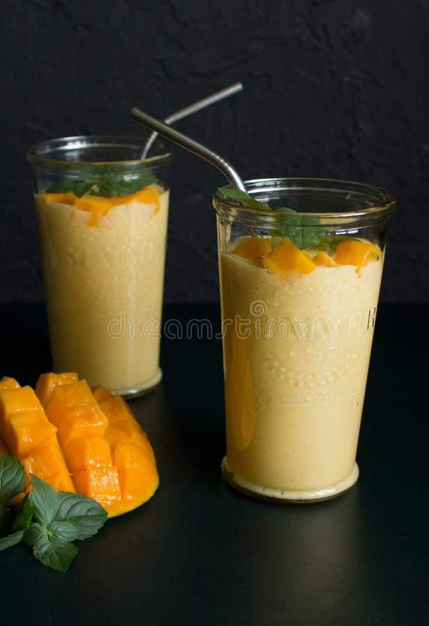 Mango smoothie / mango lassi in vintage glass cups on a dark surface with metal straws. with mint leaves and a slice of ripe and j. Uicy mango royalty free stock image