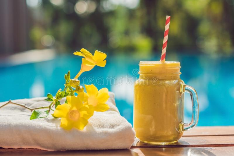 Mango smoothies on the background of the pool. Fruit smoothie - healthy eating concept. Close up of detox smoothie with royalty free stock photo