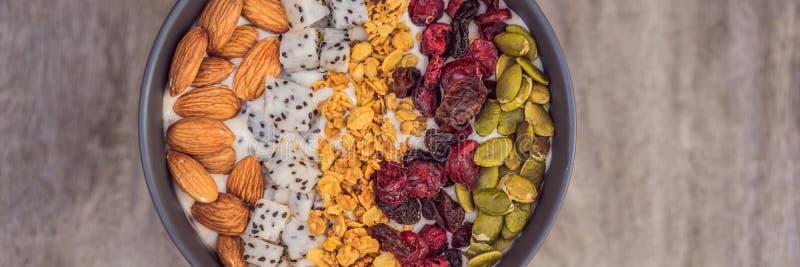 Mango Smoothies rollen mit Mandel, Drachefrucht, getrockneten Kirschen, Kürbiskernen und Granola auf hölzerner Hintergrund FAHNE lizenzfreie stockfotografie