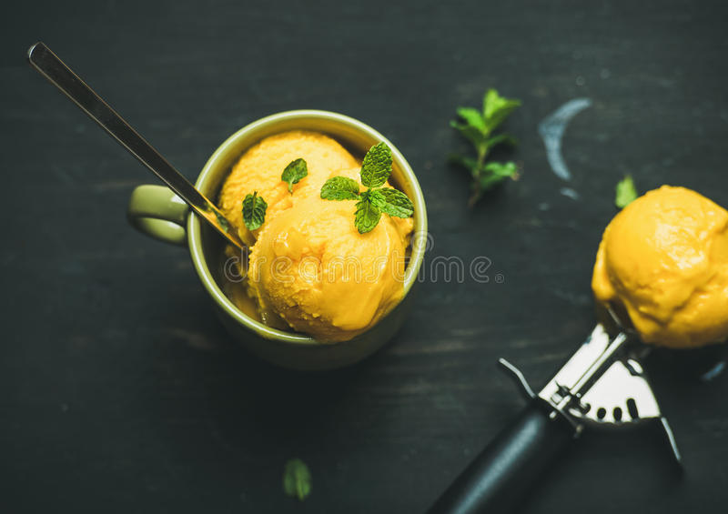 Mango sorbet ice cream scoops with mint, top view royalty free stock images