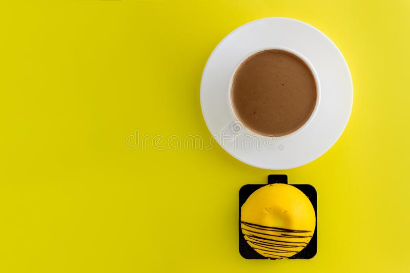 White cup of hot coffee isolated on yellow background. Mango sweet cake. White cup of hot coffee isolated on yellow background dessert cappuccino aroma steam stock photos