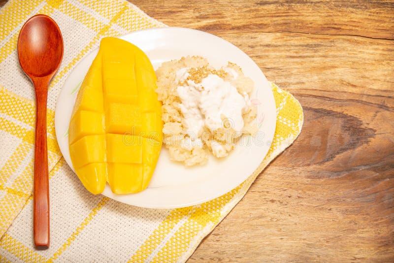 Mango tailandés y arroz pegajoso con los postres de la leche de coco en el plato blanco con el fondo de madera El mango es la fru imagen de archivo