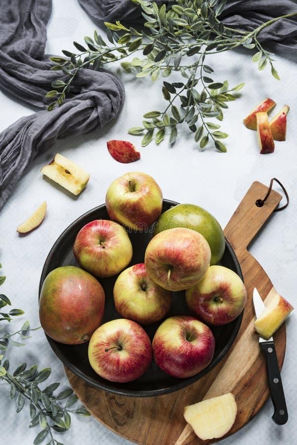 Mango und Äpfel auf Schwarzblech, Schneidebrett stockbild