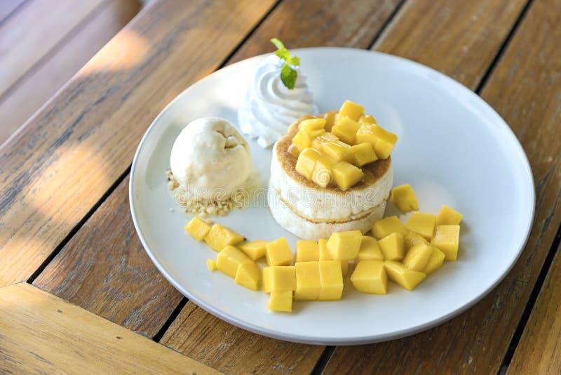 Mango und Vanilleeis mit flaumigem Kuchen in der weißen Platte stockfoto