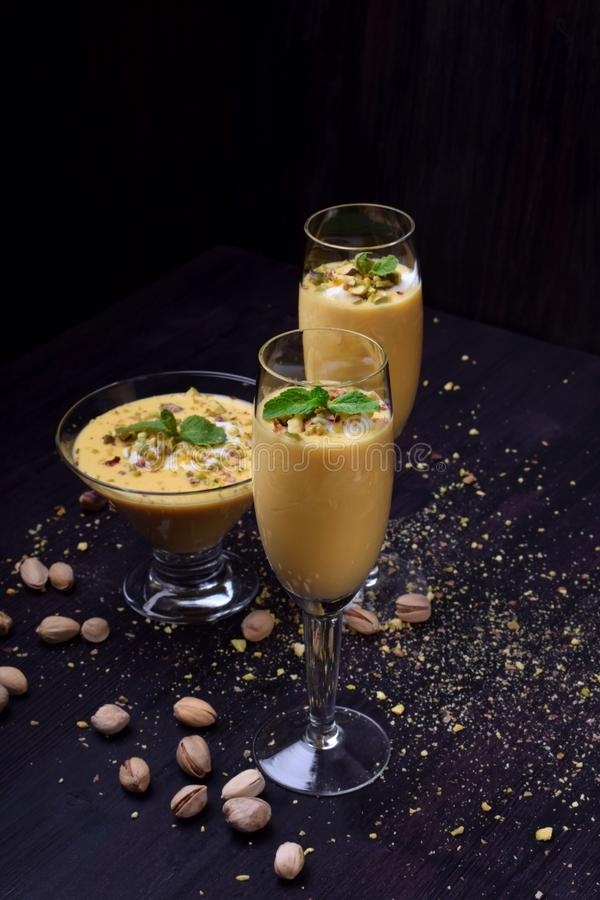 Mango yogurt dessert in glasses topped with pistachios and mint royalty free stock image
