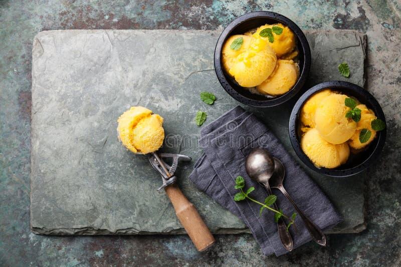 MangoEiscremesorbet mit tadellosen Blättern und Löffel für Eiscreme lizenzfreies stockbild