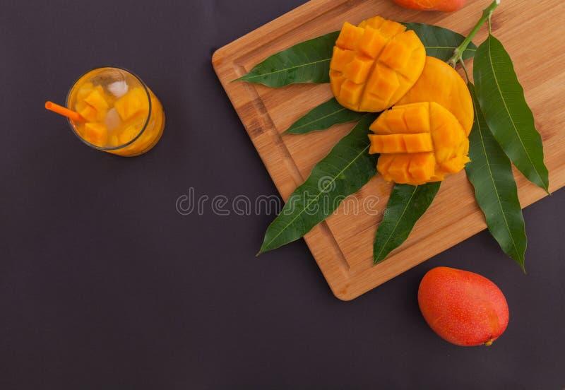 Mangofrukt och mangodrink på träskärbrädan Begrepp för tropisk frukt med ett enormt belopp av negativt utrymme för royaltyfri bild
