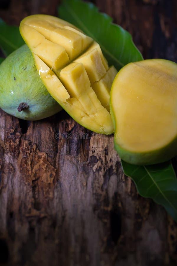 Mangofrukt och mangokuber på trätabellen royaltyfri foto