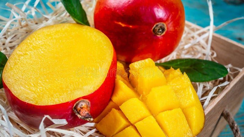 Mangofrukt och mangokuber på trätabellen Top beskådar royaltyfri bild