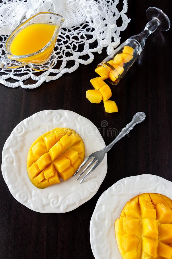 Mangofruktkuber och mangofruktsaftpuré på mörk träbakgrund royaltyfria foton